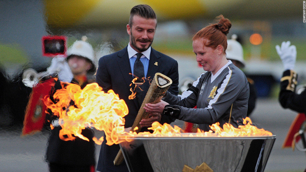 Former England footballer David Beckham, left, lights the Olympic torch upon its arrival at RNAS Culdrose Air Base in Cornwall, southwest England, on Friday, May 18.