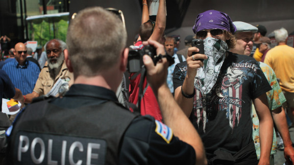 A police officer and a protester face off with cameras in Chicago during a demonstration organized by National Nurses United on Friday, May 18. Friday was the fifth day of protests leading up to the NATO summit.