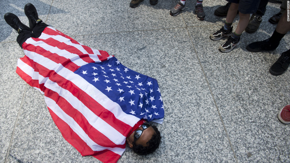 An Occupy Wall Street protester in Chicago covers himself with an American flag after a march through downtown Chicago on Friday.