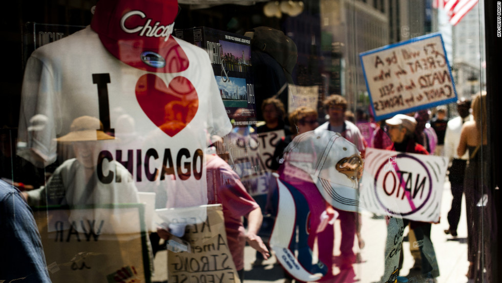 A souvenir shop window reflects protesters in Chicago on Thursday as they demand an end to NATO violence ahead of the summit.