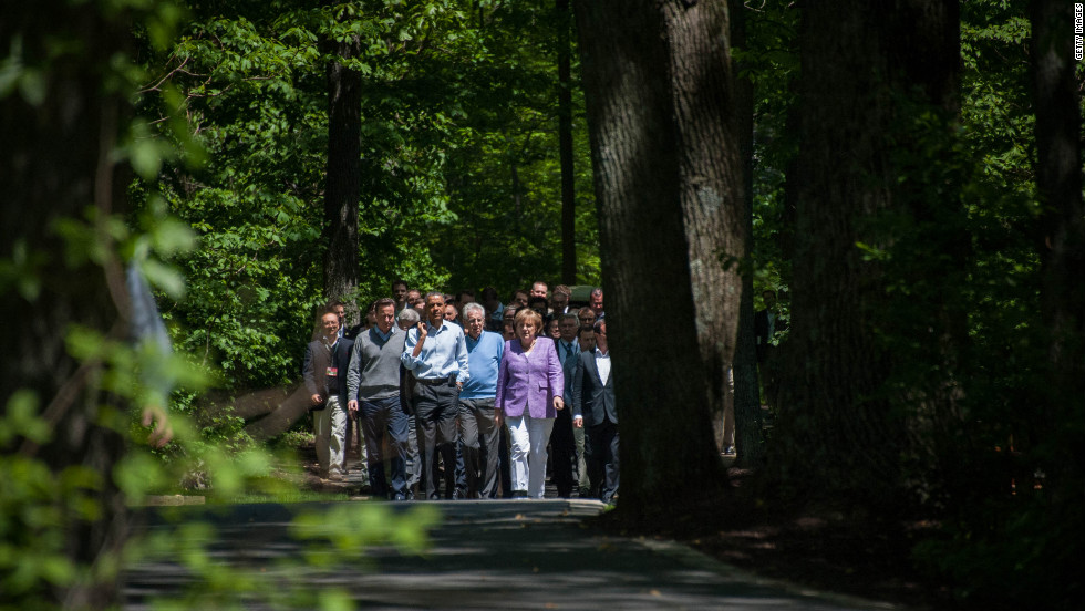 Cameron, Obama, Monti and Merkel take a stroll through the grounds of Camp David on their way to a group photo shoot.
