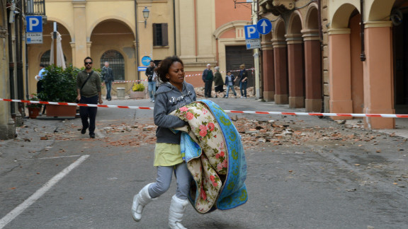 A woman carries a blanket on a blocked street following the quake in San Felice sul Panaro, Italy.