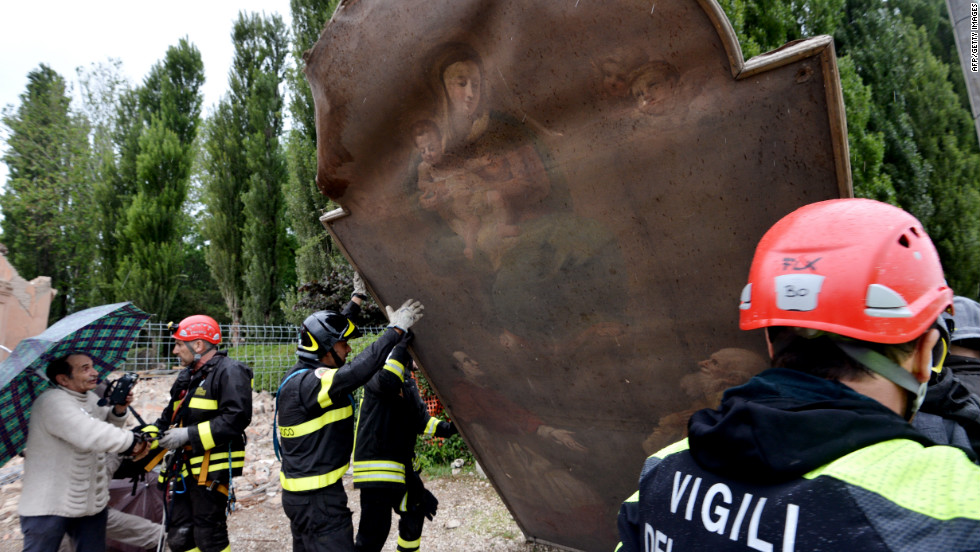 Firefighters recover a painting from a church that was destroyed by the quake in the village of San Carlo, Italy.