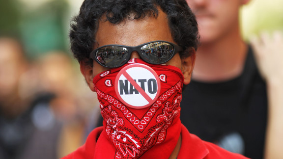 A demonstrator displays an anti-NATO button on his bandana Sunday. Largely peaceful crowds chanted, waved signs and banged drums in Chicago.