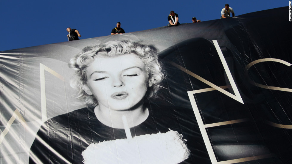 Workers set up a giant poster featuring Marilyn Monroe blowing out a birthday candle on May 13.