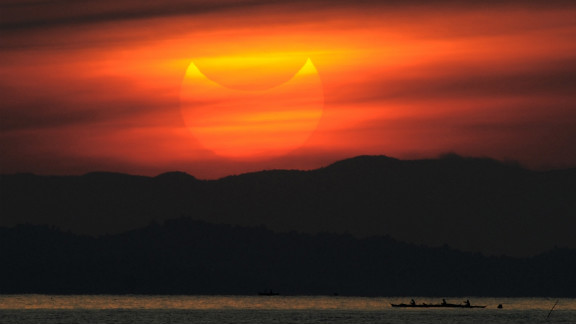 A partial solar eclipse is seen at sunrise in the coastal town of Gumaca, Philippines.