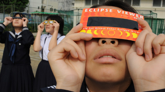 Junior high school students observe the solar eclipse through special glasses on a playground in Tokyo.
