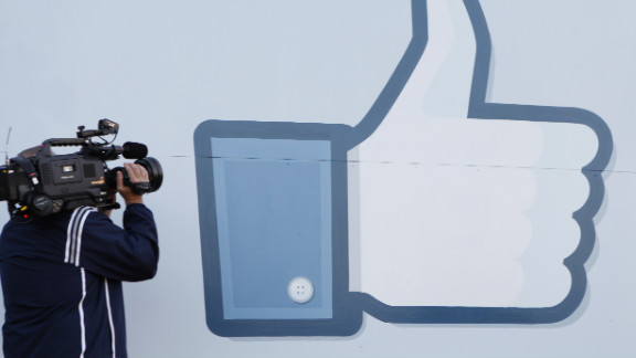 A videographer shoots the side of Facebook's Like Button logo at Facebook Headquarters in Menlo Park, California.