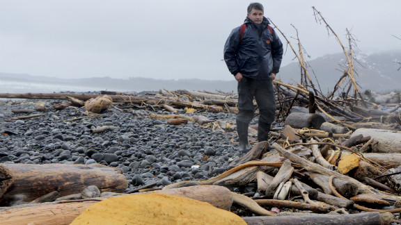 """Chris Pallister braves the elements on Montague Island to survey debris for the Marine Conservation Alliance.  He said the yellow urethane spray building foam insulation, which came from stockyards and from crushed structures in Japan, started showing up in January. """"We just never got much of that before, but if you walk up and down this beach you see big chunks,"""" he said."""