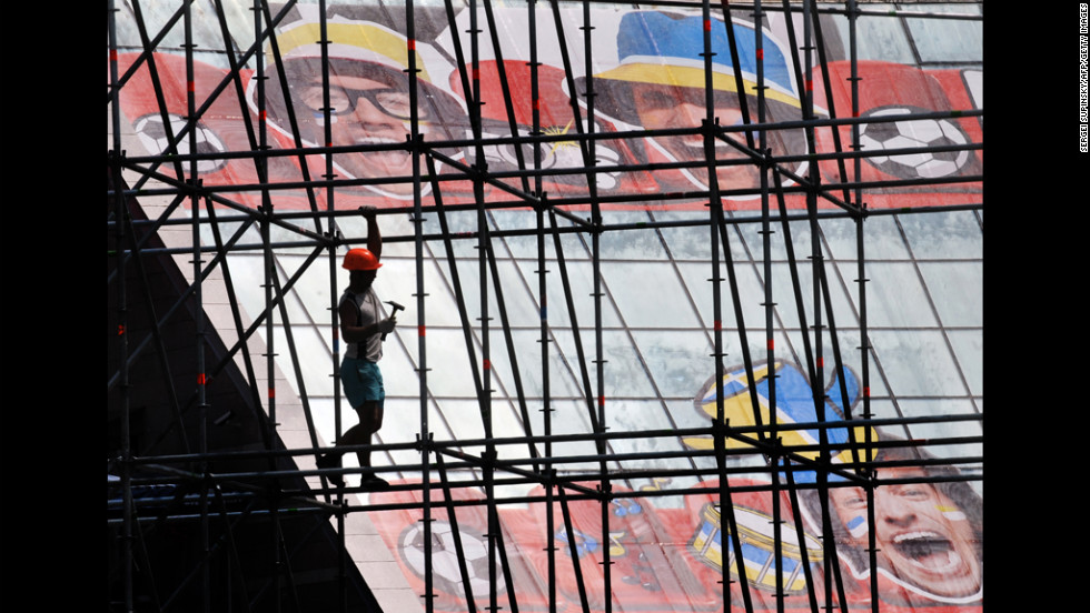 A worker walks in front of the glass walls of a building with a poster depicting soccer themes during preparations Tuesday for the EURO-2012 fan zone in Kiev, Ukraine.