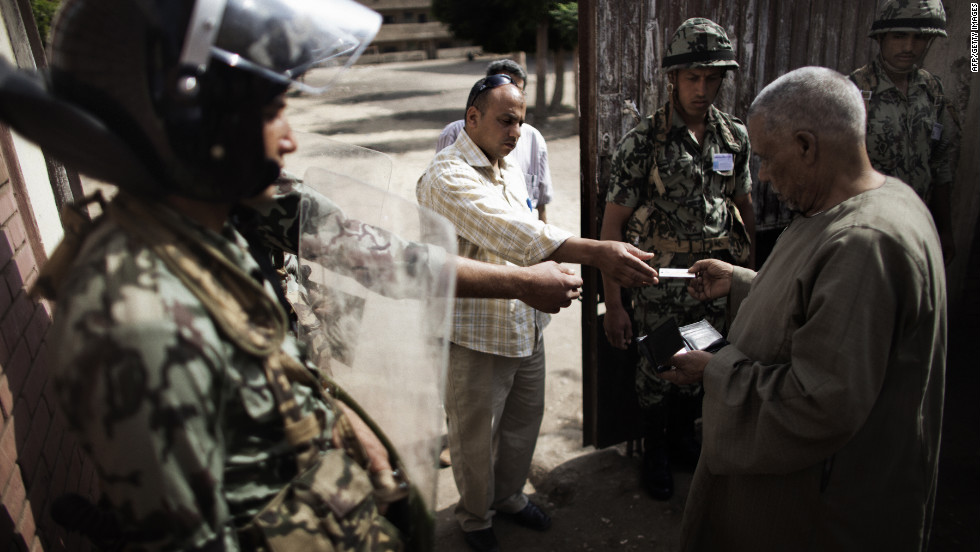 An election worker checks the identification of a voter at a polling place Thursday in Namul as Egyptian soldiers stand guard.