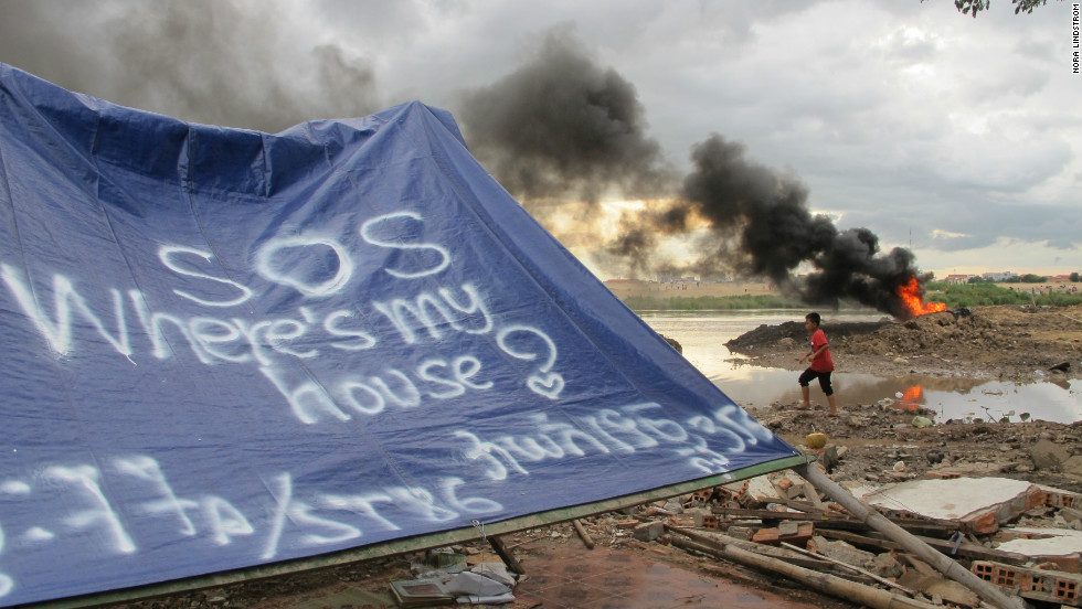 Residents of eight destroyed homes put up a tarpaulin where they used to live.