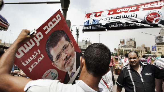 An supporter of the Muslim Brotherhood's presidential candidate holds a campaign poster in Cairo on Friday.