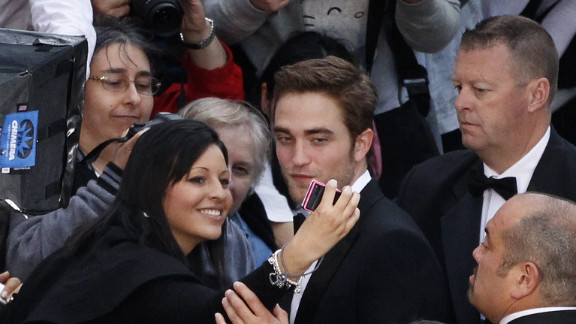 """British actor Robert Pattinson signs autographs and poses for photos with fans prior to the screening of """"Cosmopolis"""" on Saturday."""
