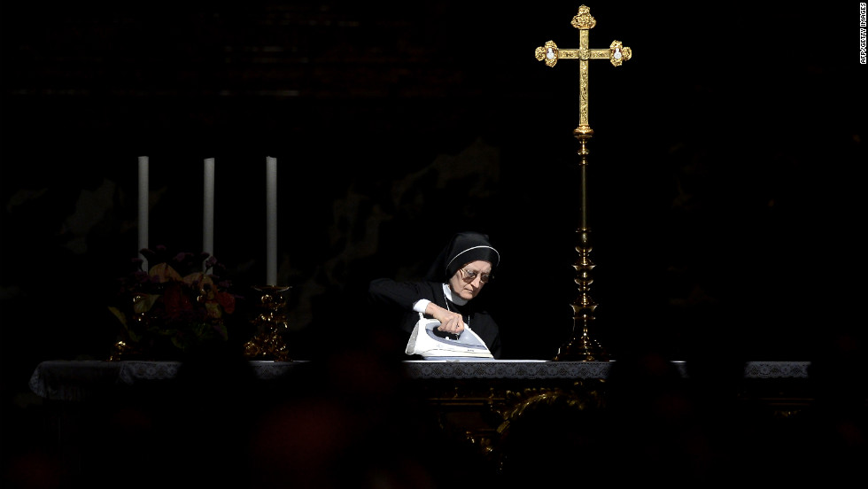A nun irons an altar cloth prior to the arrival of Pope Benedict XVI at St. Peter's Basilica in the Vatican on Sunday.