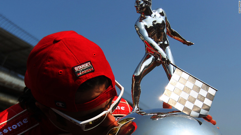 Driver Dario Franchitti kisses the Borg Warner Trophy at Indianapolis Motor Speedway on Sunday after winning his third Indianapolis 500 auto race.