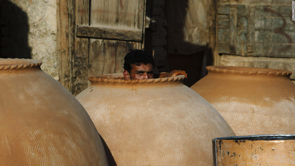 An Afghan man peeks out of a tandoor oven while building it in Kabul.
