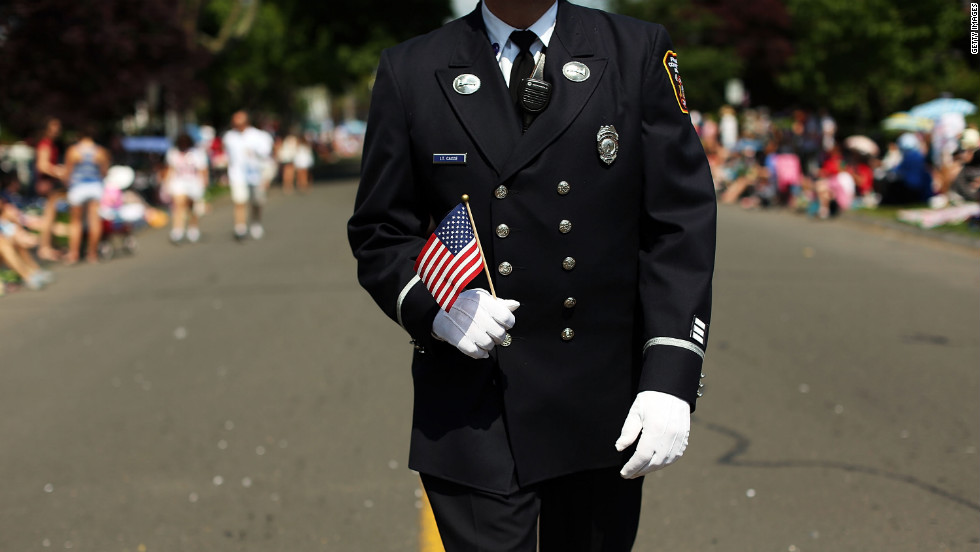 A firefighter holding a flag participates in the annual Memorial Day parade in Fairfield, Connecticut, on Monday.