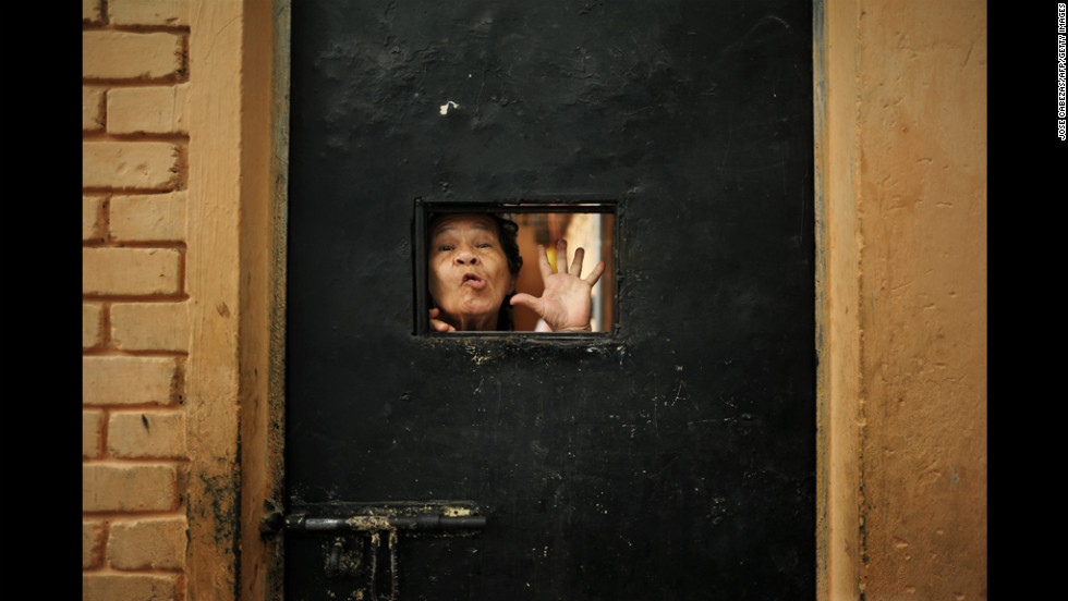An inmate gestures from her cell inside the national female prison in San Salvador, El Salvador, on Monday. Female inmates ask to join a truce declared in March by two major gangs.