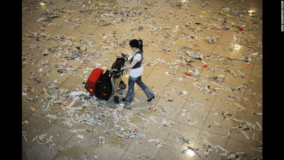 A passenger walks among trash and papers Tuesday at the airport in Barcelona, Spain, as cleaning staff strike to protest budget cuts.