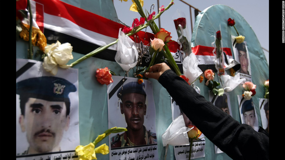 A Yemeni woman attaches a flower to a portrait of a victim of a May 21 suicide attack during a demonstration Tuesday in Sanaa.