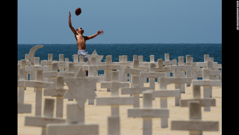 A man jumps after a ball behind the Arlington West temporary memorial built at the beach next to Santa Monica Pier in California on Monday.