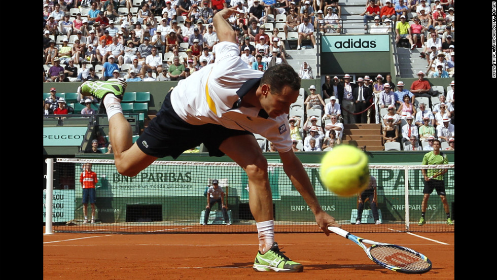 Spain's Guillermo Garcia-Lopez misses a return from France's Michael Llodra during their first-round match Monday in the French Open tennis tournament at the Roland Garros stadium.