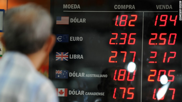 A man watches the foreign currencies exchange rate on the placard of a bureau de change in Rio de Janeiro, Brazil.
