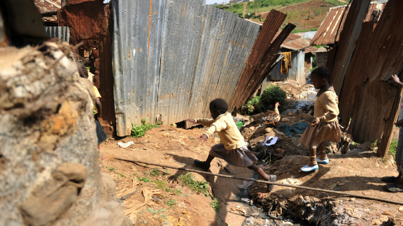 A young girl jumps across a ditch in front of her home in Kibera, the Kenyan squatter settlement that is one of Africa