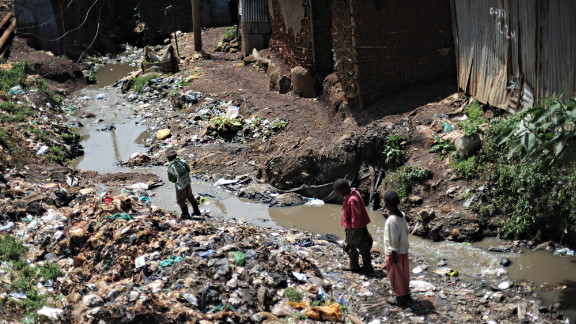 Children in Kibera make their way through the neighborhood across mounds of trash. Kibera suffers from a lack of waste management and santiation services, alongside a host of other critical infrastructure.