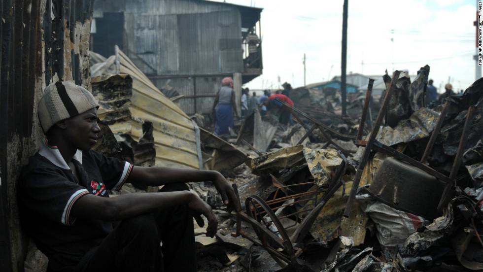A resident of Kibera sits among the remains of houses that were razed by a fire in March, leaving about 200 families homeless.