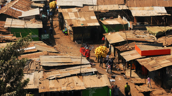 A man carries plastic containers through Kibera on his way to sell them to be recycled. Residents of Kenya
