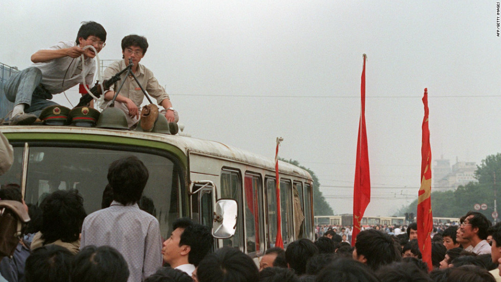 Students on the roof of a bus display items confiscated from PLA soldiers after they forced troops to retreat from the area on June 3, 1989.