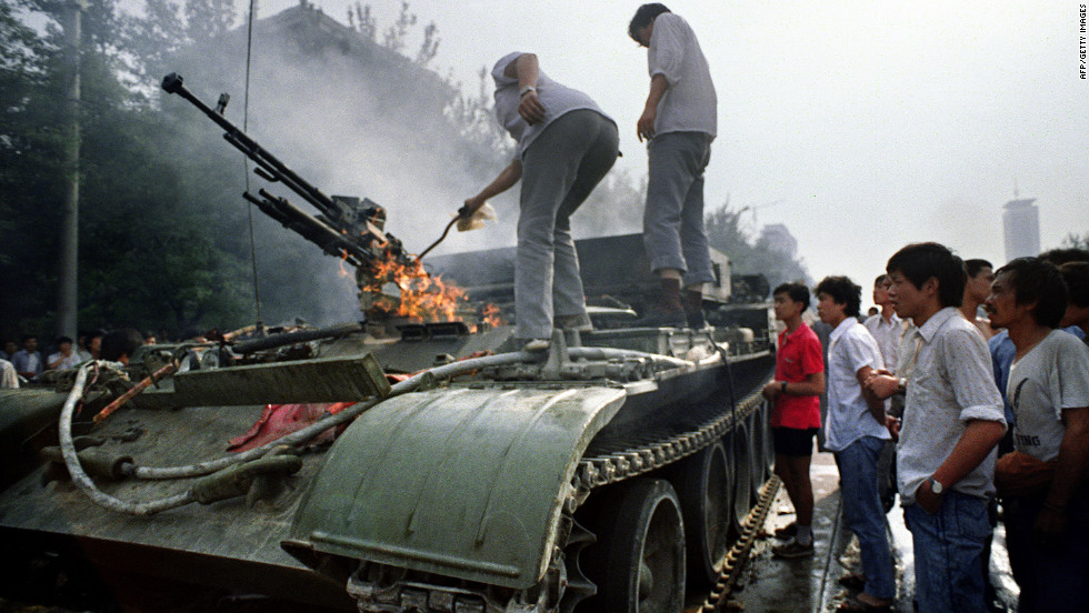 Residents inspect an armored personnel carrier set on fire by rioters.