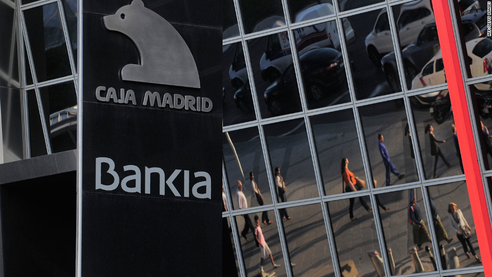 Commuters are reflected on the headquarters of Bankia SA on May 29, 2012 in Madrid, Spain. Spanish borrowing costs have increased after the government announced a rescue plan for Bankia involving more public debt.