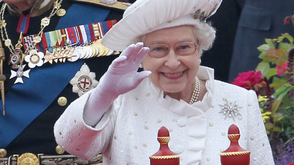 Britain's Queen Elizabeth II waves to thousands along the Thames as the royal barge makes its way down the river.