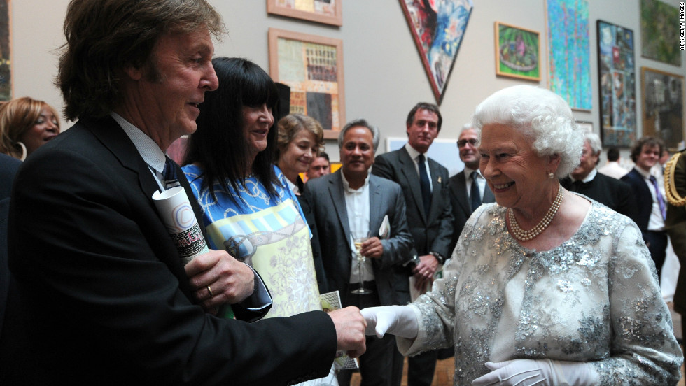 Britain's Queen Elizabeth II meets Paul McCartney and his wife Nancy Shevell as she visits the Royal Academy of Arts in central London