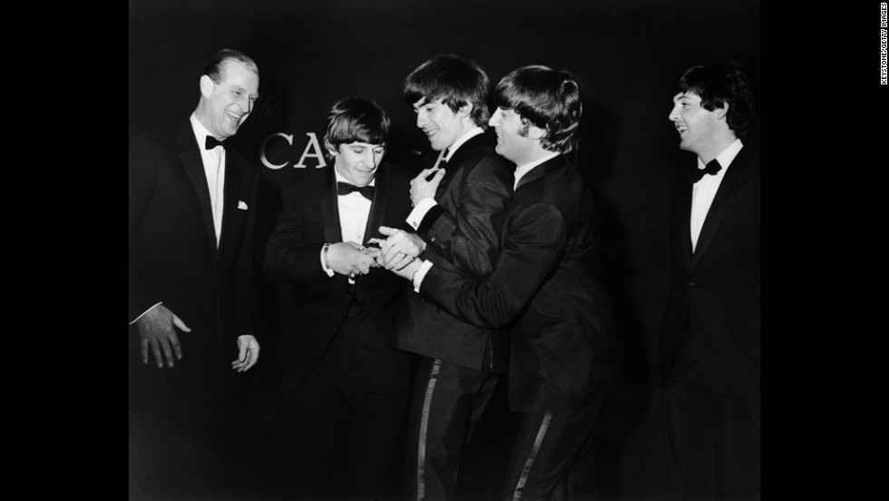 Prince Philip laughs as the Beatles fight over the Carl Alan Award he presented to the band in March 1964.