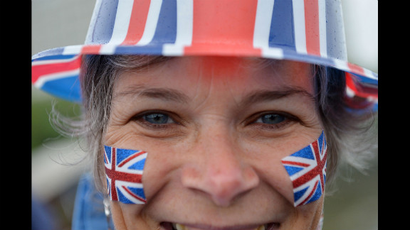 A woman watches the River Pageant from the Westminster Bridge.