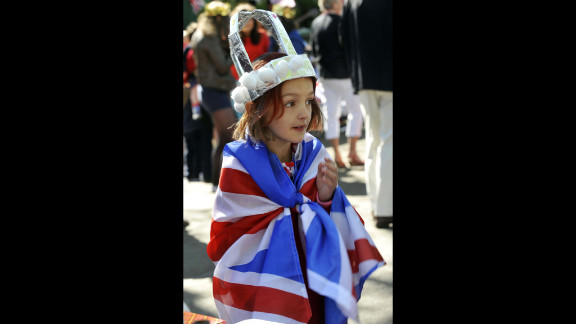 A young girl wearing a crown is wrapped in a Union flag during a street party to celebrate the Queen