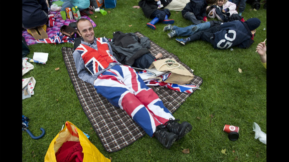 A man watches the River Pageant projected on a screen in Battersea Park.