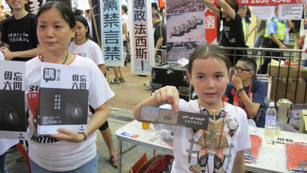 "Volunteer Nicole Lai, 7, hands out bookmarks to passersby at the League of Social Democrats booth alongside her mother (L).  ""Many people died so I'm here to pay my respects,"" she says."