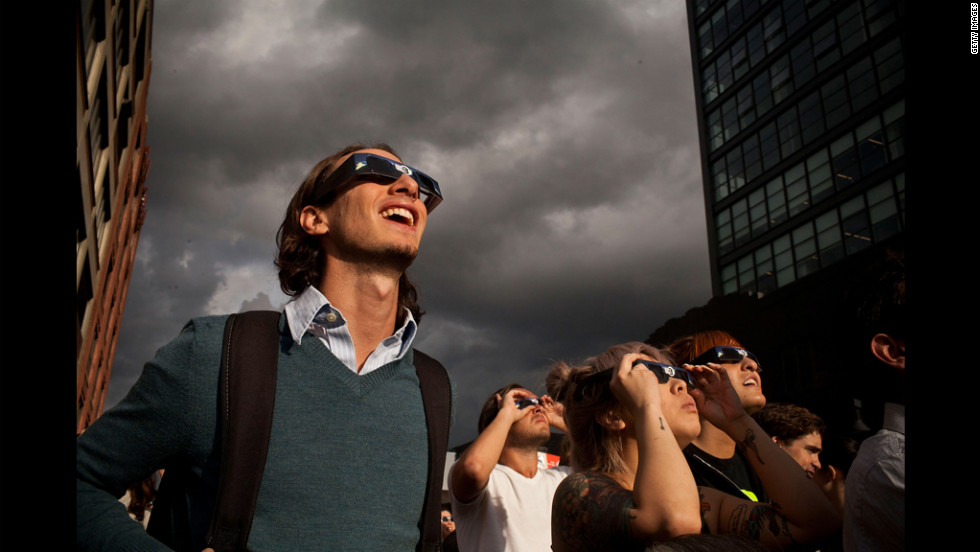 New Yorkers gather to witness the event on Tuesday. Watching without special glasses will permanently damage your eyes, experts say.