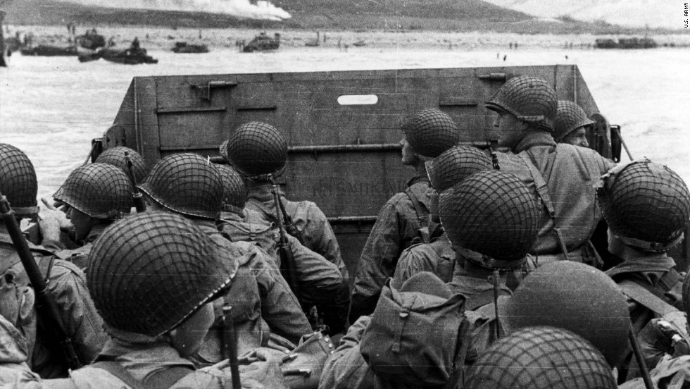 US troops huddle behind the protective front of their landing craft as it nears a beachhead in France. Smoke in the background is naval gunfire giving cover to troops on land. Germans rained mortars and artillery down on Allied troops, killing many before they could even get out of their boats. Fighting was especially fierce at Omaha Beach, where Nazi fighters nearly wiped out the first wave of invading forces and left the survivors struggling for cover.