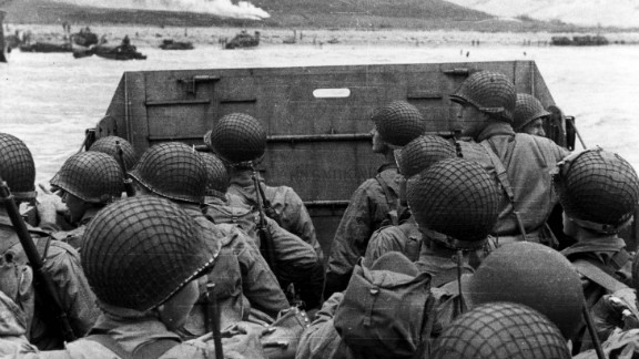 U.S. troops huddle behind the protective front of their landing craft as it nears a beachhead. Smoke in the background is naval gunfire, giving cover to troops on land.