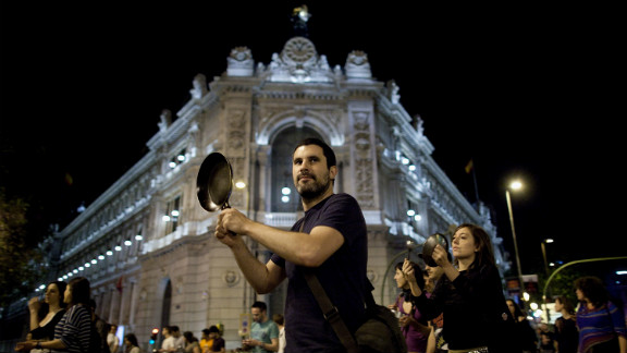 A protester hits a pot while walking past the Bank of Spain on May 15, 2012 in Madrid, Spain. Spain
