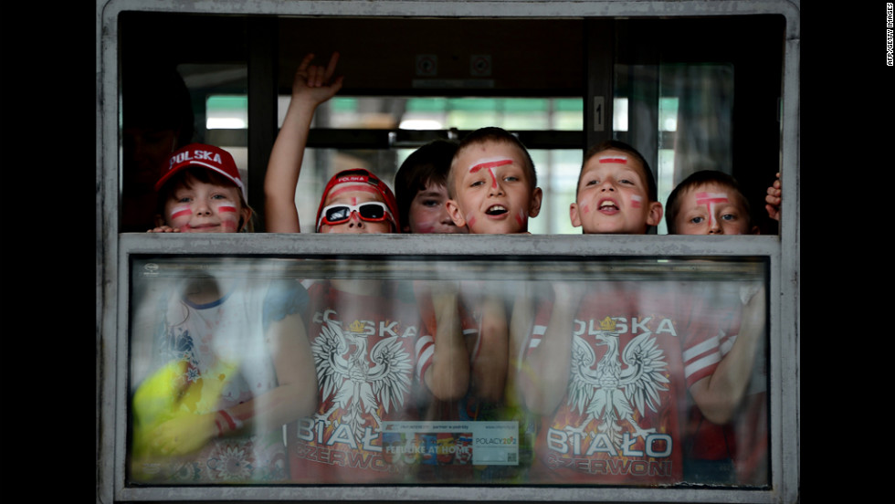 Fans of Poland's national soccer team wave from a train window.