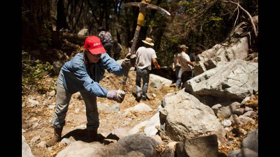 Volunteer Melinda Brooks uses a pickaxe to break up rocks.