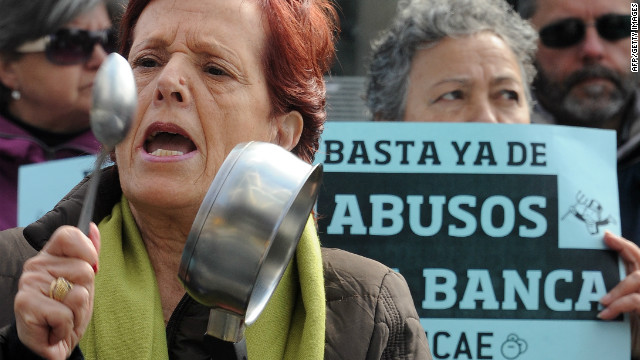 "A protester holds a banner reading ""Enough of the banking abuses"" during a demonstration outside Bankia HQ in March."