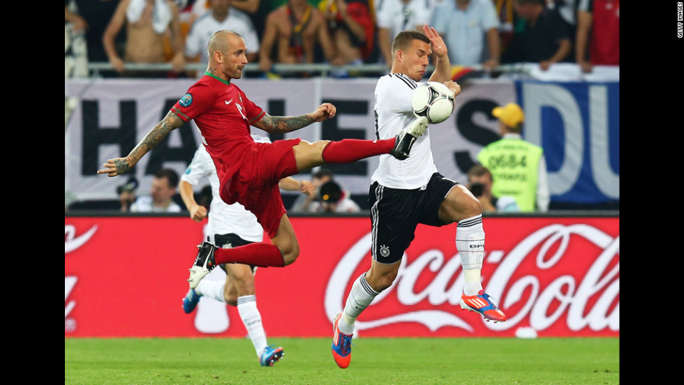 Lukas Podolski of Germany and Raul Meireles of Portugal battle for the ball.
